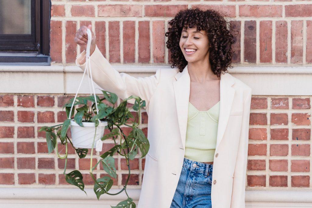 woman raising hanging plant